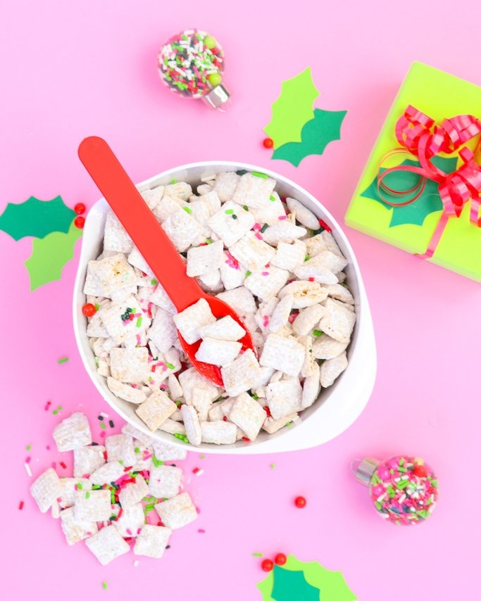 White Chocolate Christmas Puppy Chow Recipe - Christmas Muddy Buddies on pink background with wrapped presents around