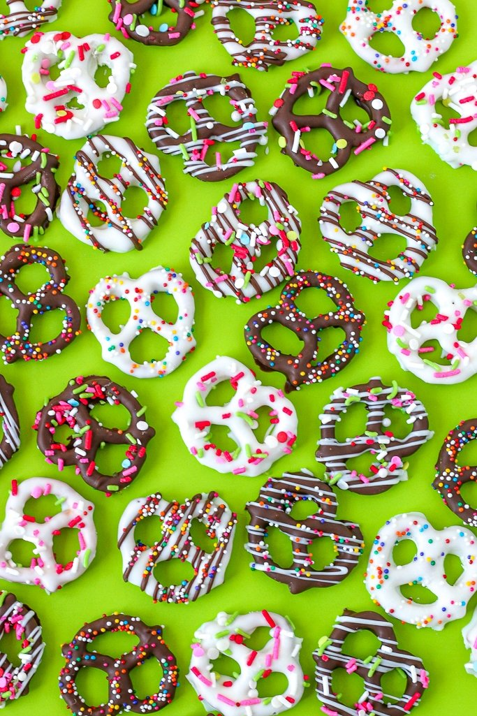 Tray of finished sprinkled homemade chocolate covered pretzels recipe on green background