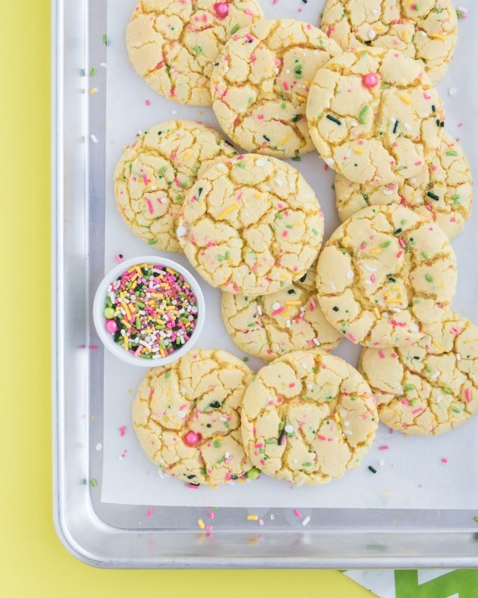 Lemon Cake Mix Cookies on silver baking sheet and yellow background