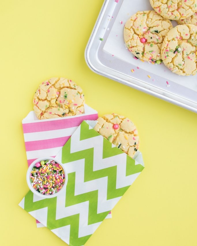 Lemon Cake Mix Cookies with sprinkles in goodie bags on yellow background