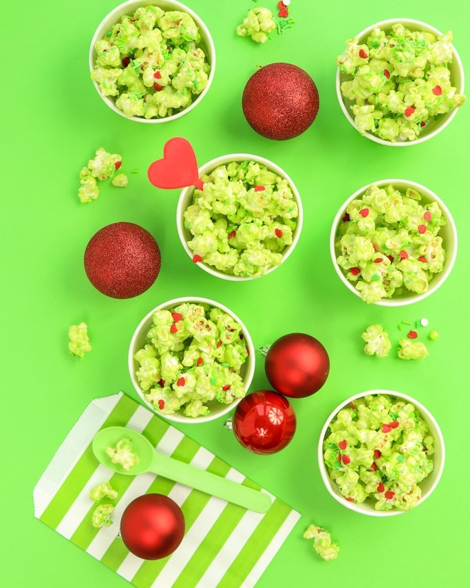 Grinch Popcorn recipe in green striped treats cups on lime green background with red Christmas ornaments.