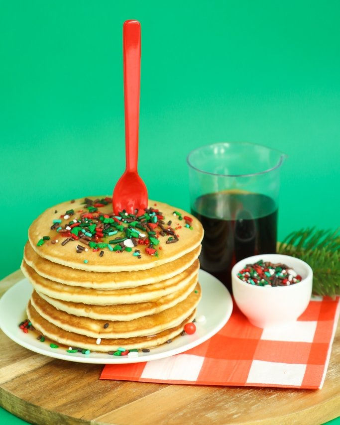Lumberjack sprinkles topped pancake stack on wood plate