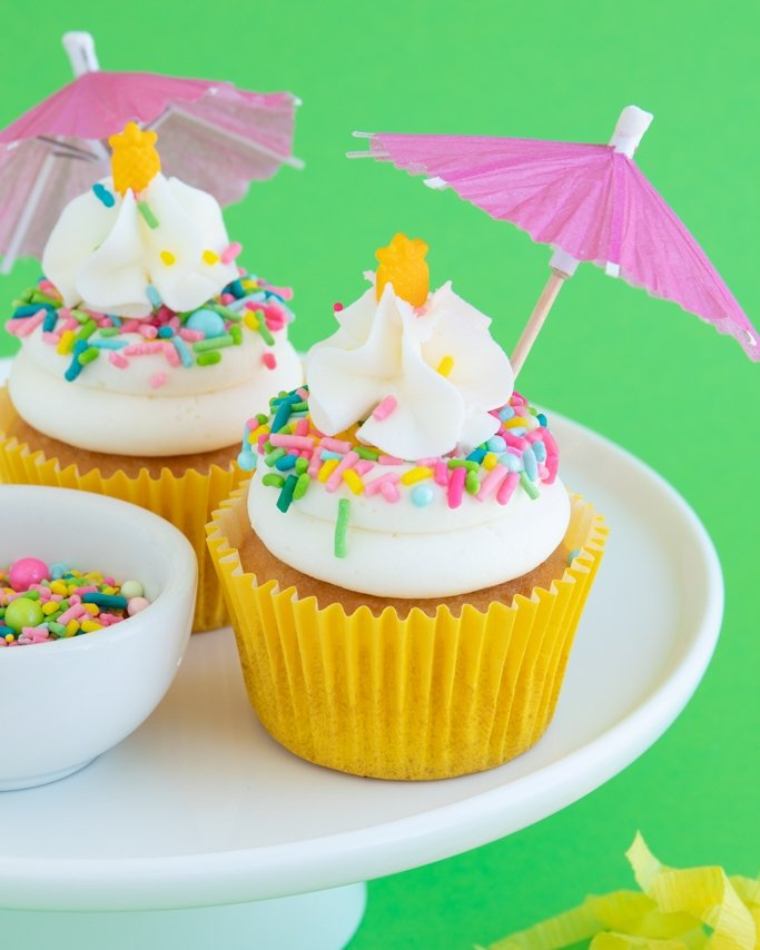 Pina Colada Cupcakes on white cake plate on green background