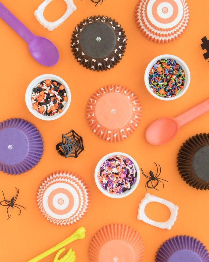Halloween Party Supplies - cupcake liners, halloween sprinkles, ice cream spoons on orange background