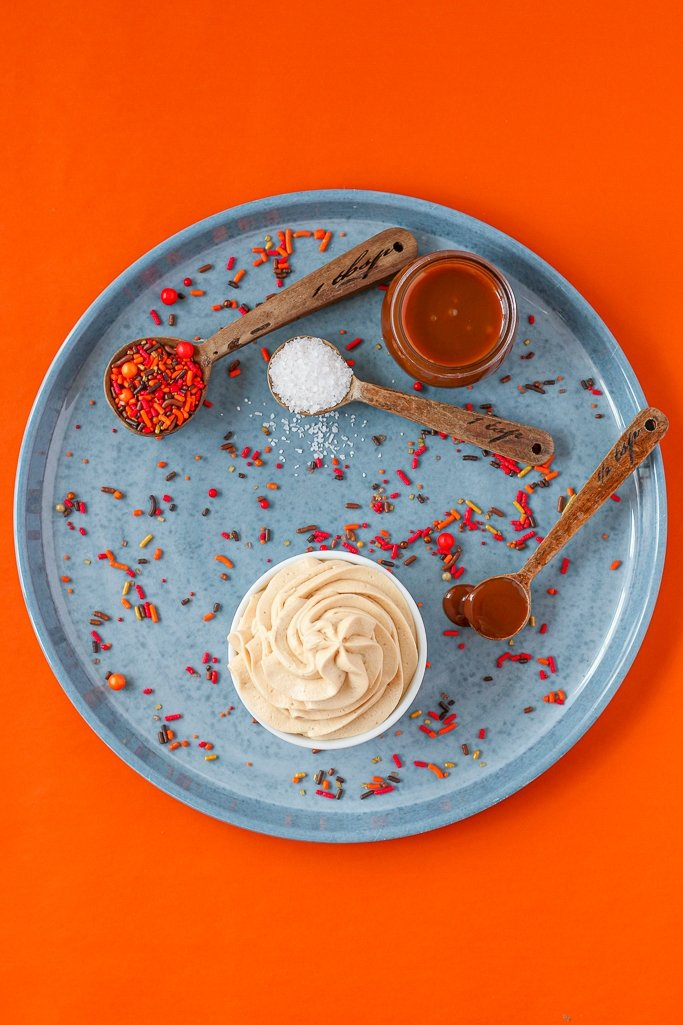 overhead photo of salted caramel buttercream frosting with fall sprinkles around