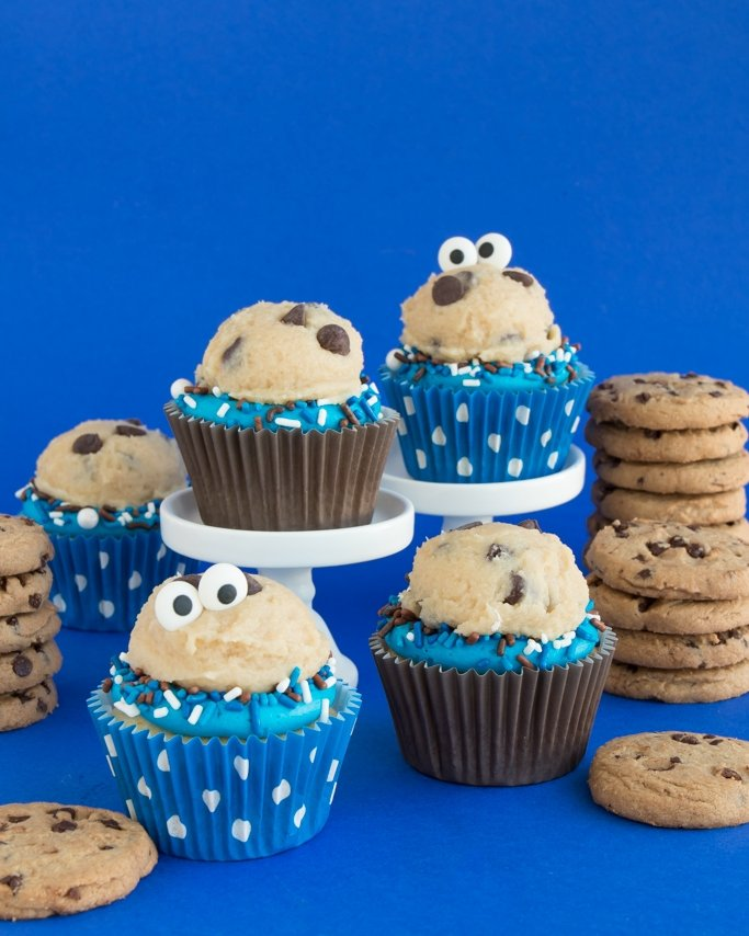 Chocolate Chip Cookie Dough Frosting Recipe - Cookie Monster Cupcake Idea on blue background and cookies stacked behind