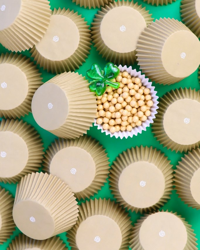 St. Patrick's Day Party Supplies - Gold cupcake liners on green background