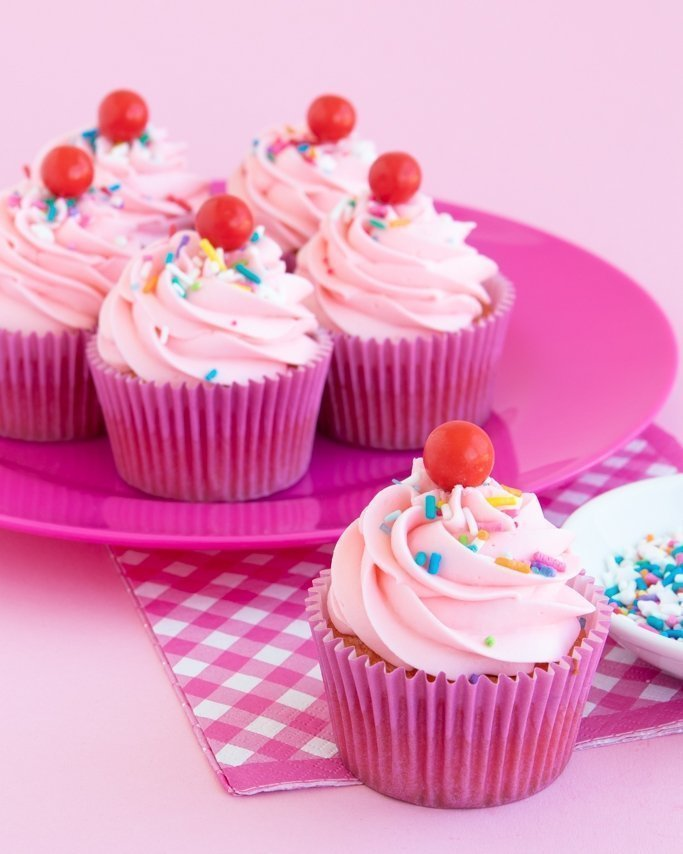 closeup of pink strawberry funfetti cupcakes topped with strawberry frosting