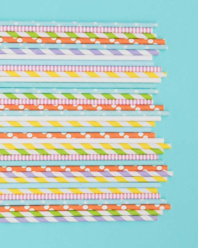 Assorted Rainbow Paper Straws on blue background - Slumber Party Ideas