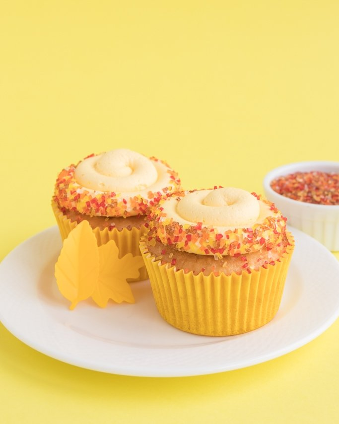 Fall Cupcakes With Fall Sprinkles on white dish and yellow background