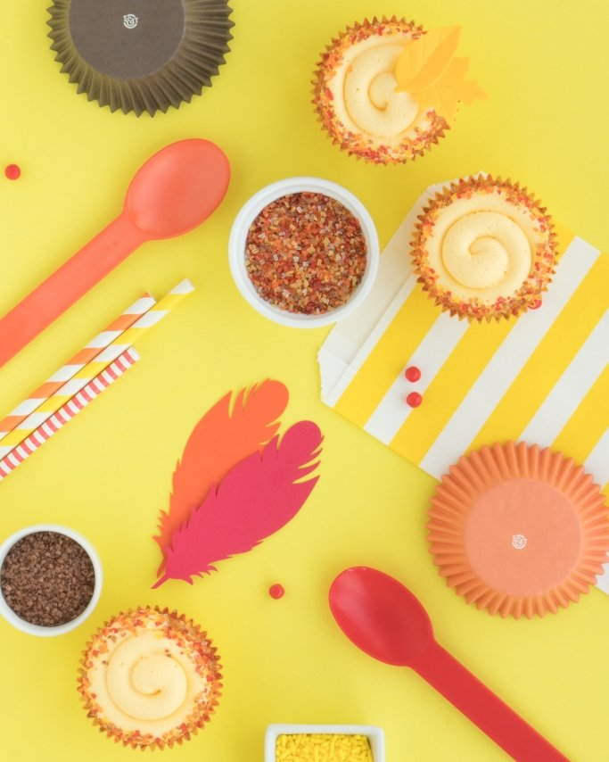 Thanksgiving party supplies laid on yellow background with orange, brown, red, and yellow assorted party supplies