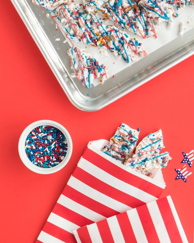 Patriotic White Chocolate Pretzel Bark - Easy 4th of July Dessert in red stripe goodie bags on red background