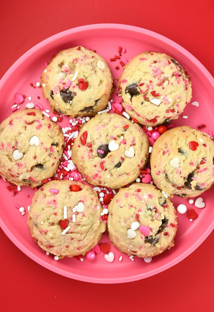 Valentine Chocolate Chip Cookies with sprinkles on pink round plate on red background