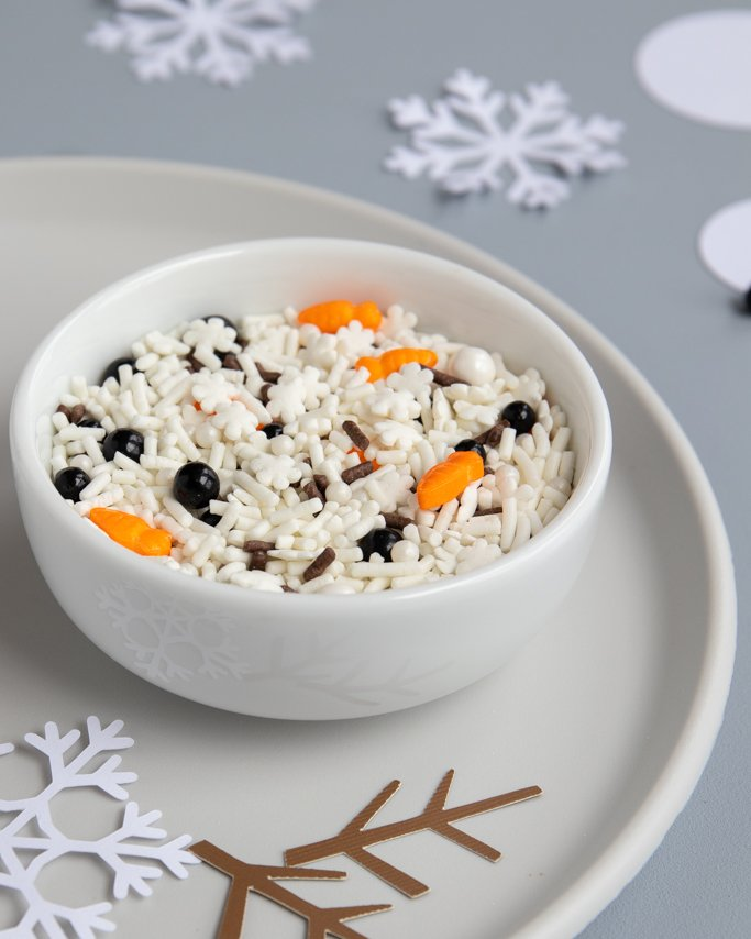 melted snowman sprinkles in white dish with paper cutout winter confetti