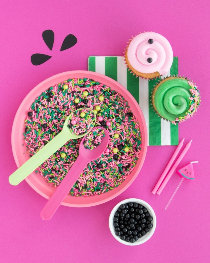 Watermelon Sprinkles on pink plate and pink background with other sprinkles and cupcakes around