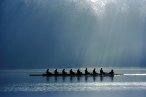 Canoe team on river during a cloudy blue day in synchrony.