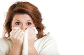 Woman gasping with blanket up to face
