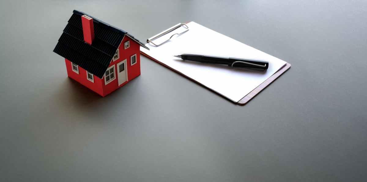 clipboard with pen near mini cardboard house