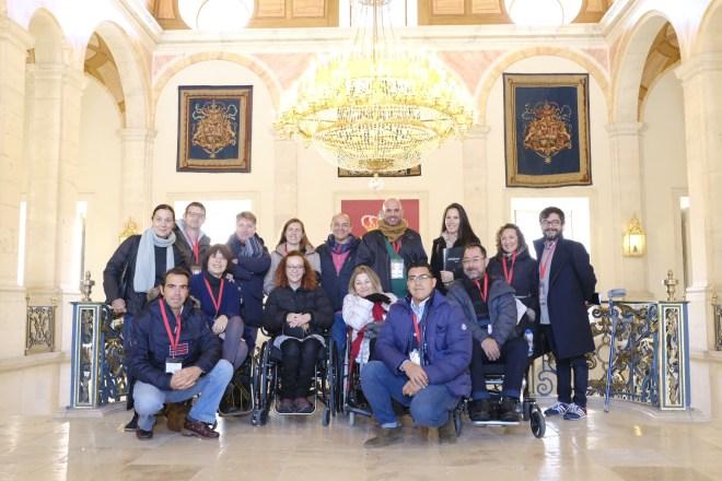 El grupo dentro del palacio real, se ven unos escudos y una gran lámpara.