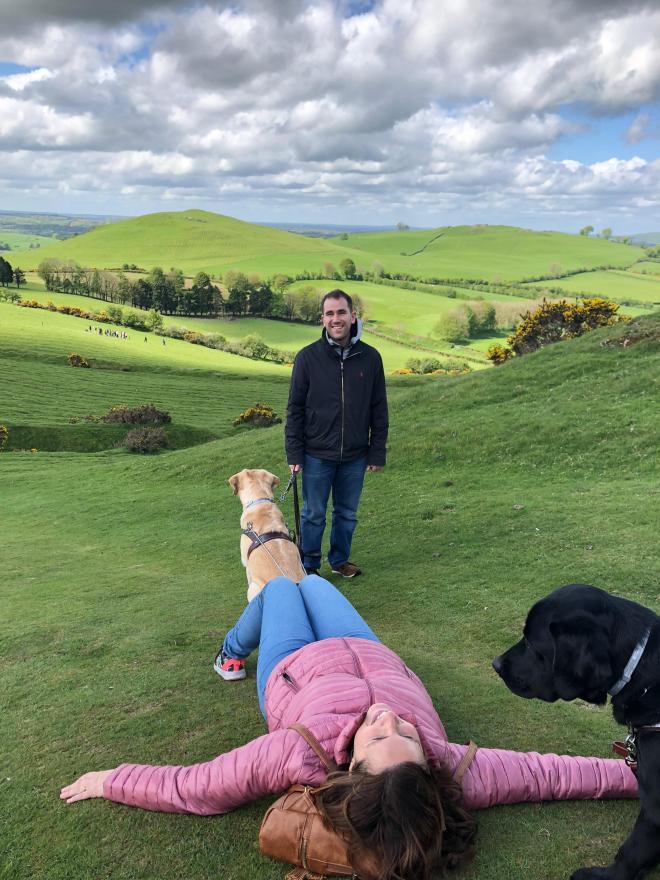 Núria echada en un prado, Juanjo de pie riendo y vistas de montañas muy verdes.