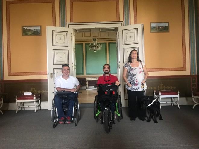 Dos chicos en silla de ruedas y una chica ciega con su perro guía, todos en el interior de la villa de Ludwigshöhe