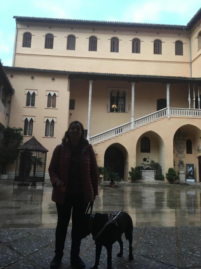 Núria con su caracol viajero de peluche y su perro guía en el patio del Palau Ducal