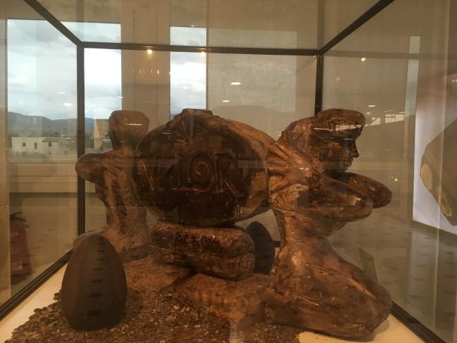 Una vitrina que contiene dos figuras de chocolate que sujetan un óvalo donde hay escrito: Valor