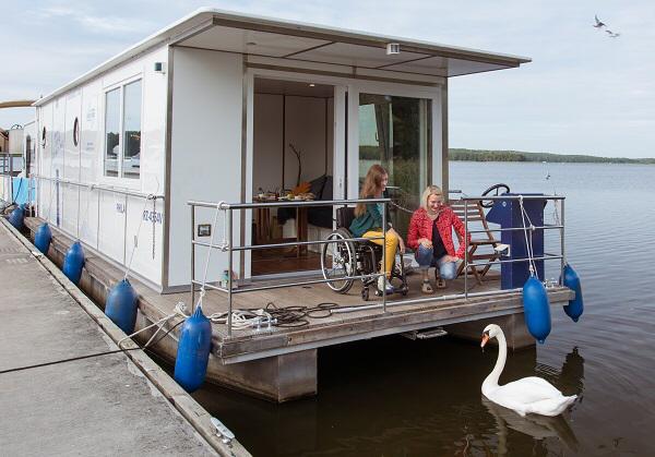 Casita flotante donde se ve a dos chicas, una en silla de ruedas que están dando de comer a un cisne blanco. Imagen corttesía de Turismo de Brandenburgo