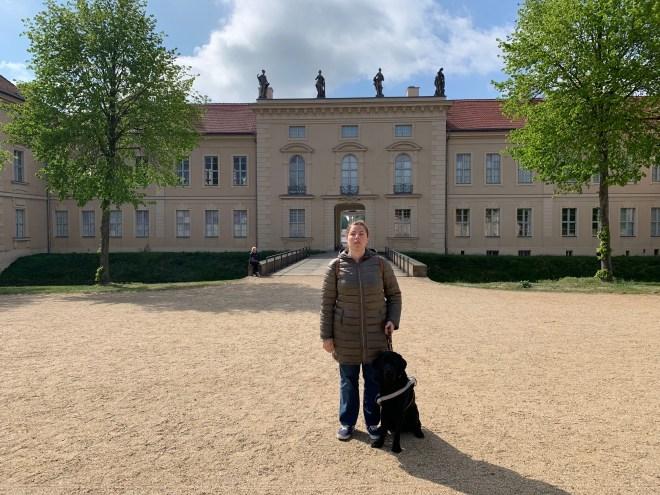 Núria con su perro guía en la puerta del palacio de Rheinsberg