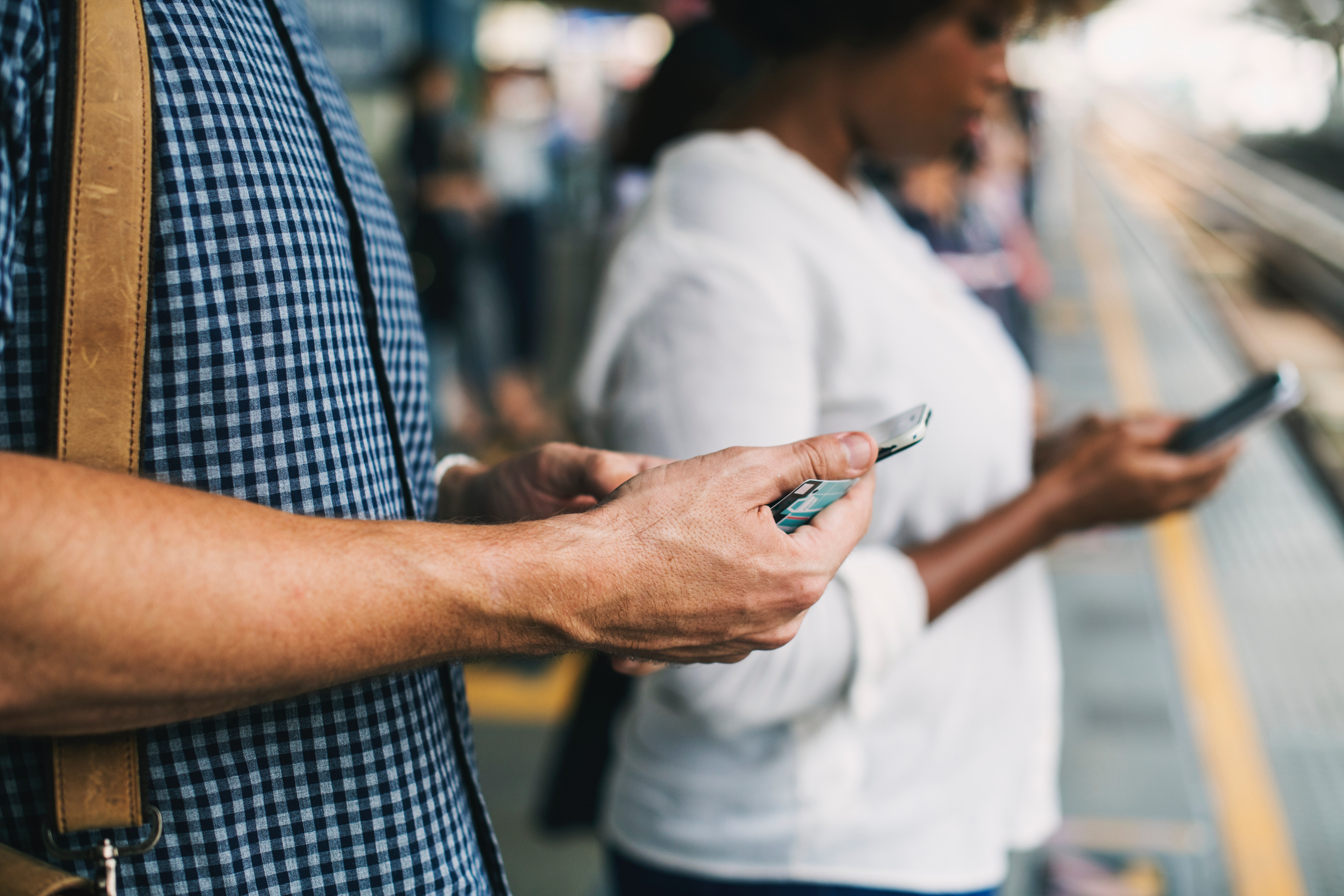 Two people look at their phones.