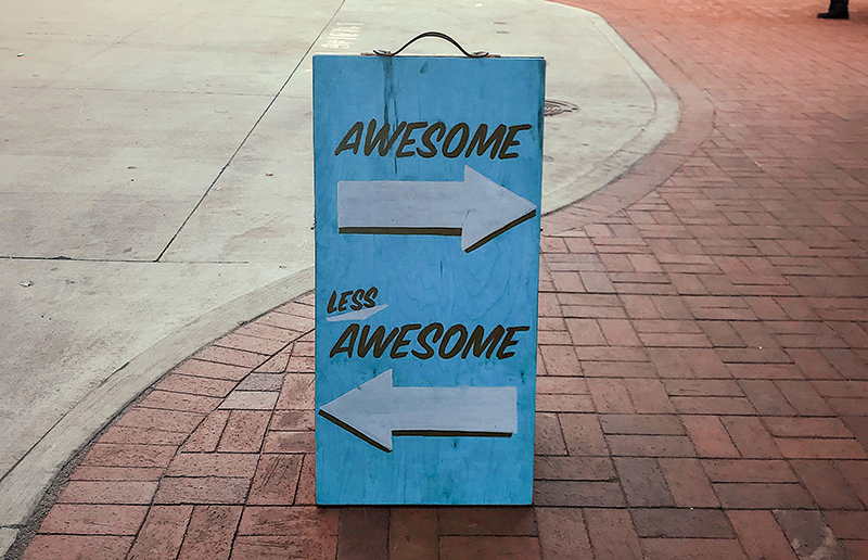 A street sign that says awesome and less awesome with arrows pointing different directions.
