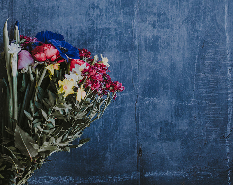 A bouquet of flowers in front of a blue wall. Though flowers could be a form of customer love, how you communicate is as well.