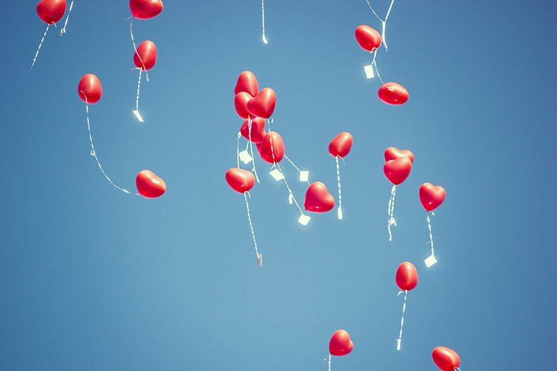 Heart-shaped balloons in the blue sky.