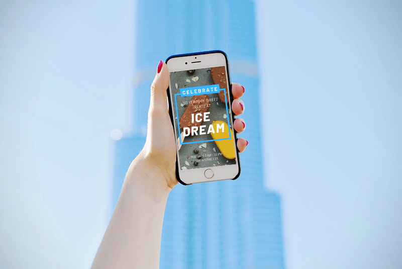 A woman holding a phone up with a building in the background.
