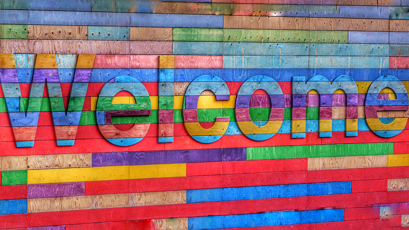 A woodcut welcome sign in many colors.