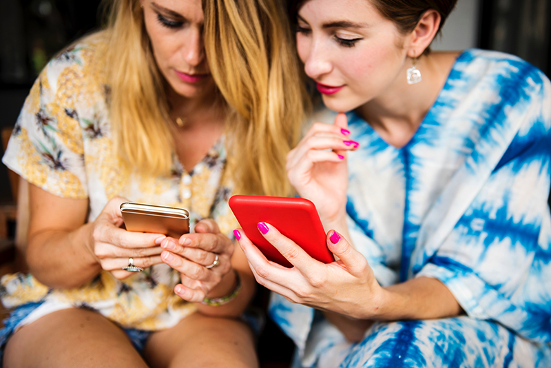 Two women sitting next to each other, each with a phone out.