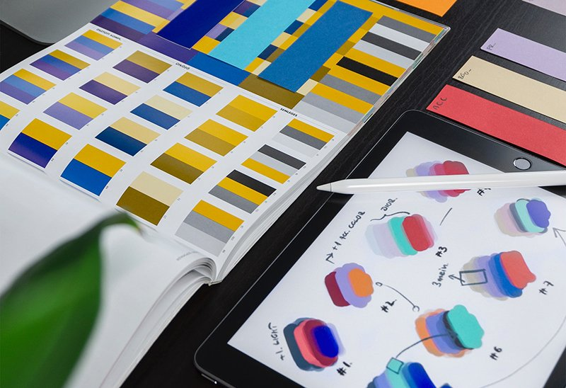 A book of color palettes with color samples and a tablet open with color samples.