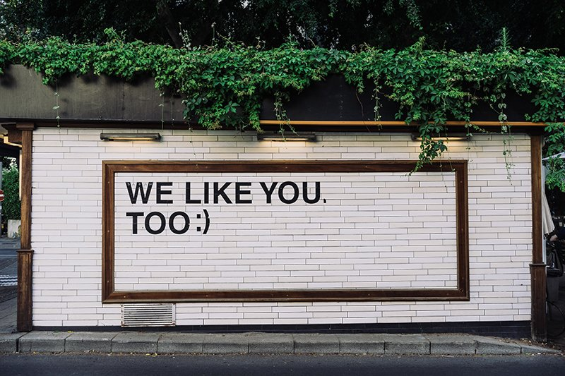 A sign painted on a white brick wall that says we like you too.