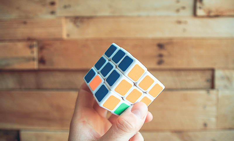 A partially solved rubik's cube that is orange, blue, and green.