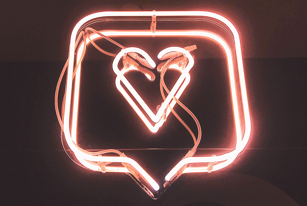 A neon sign with a heart inside a text bubble
