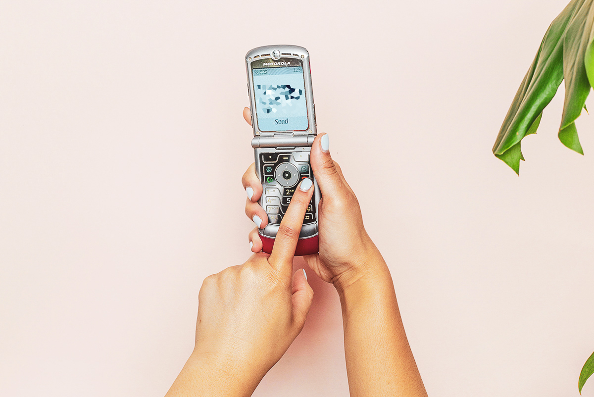 A person with light blue nail polish typing a text on a silver flip phone.