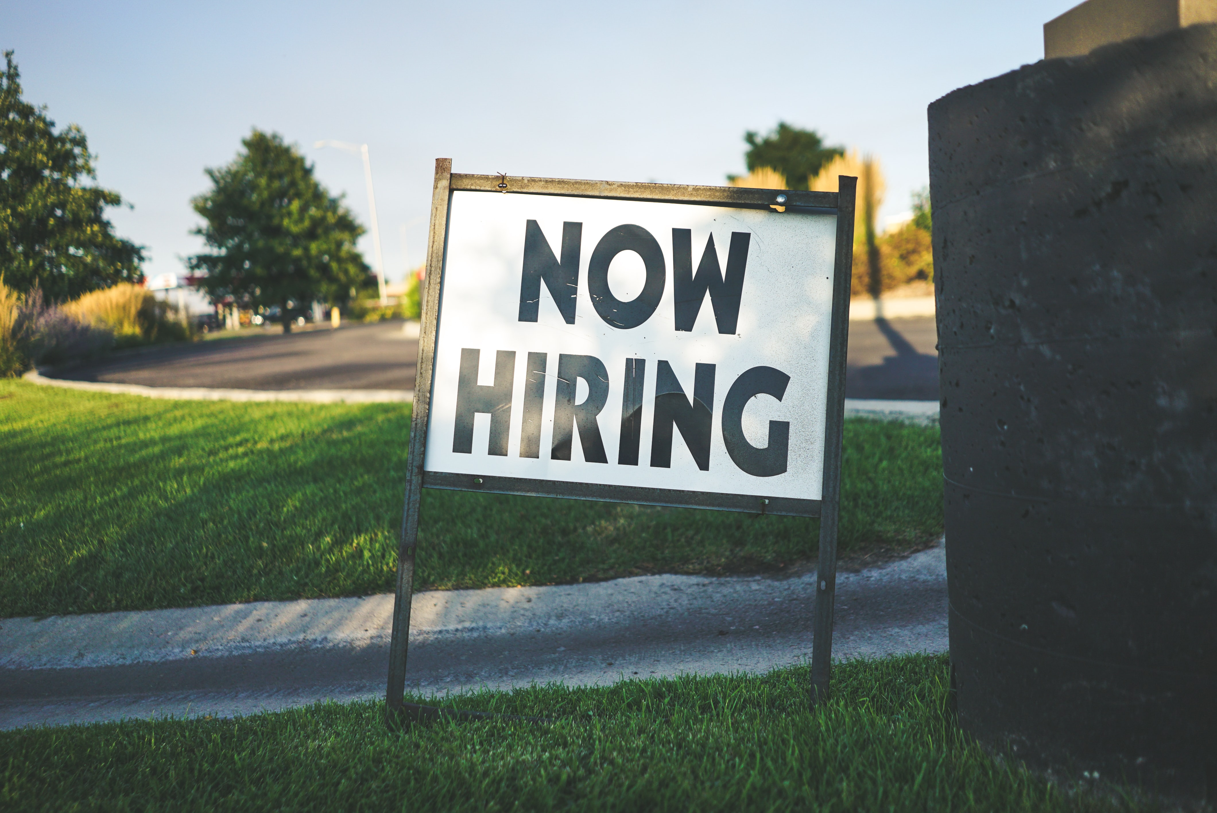 A white sign with large black lettering that says now hiring.