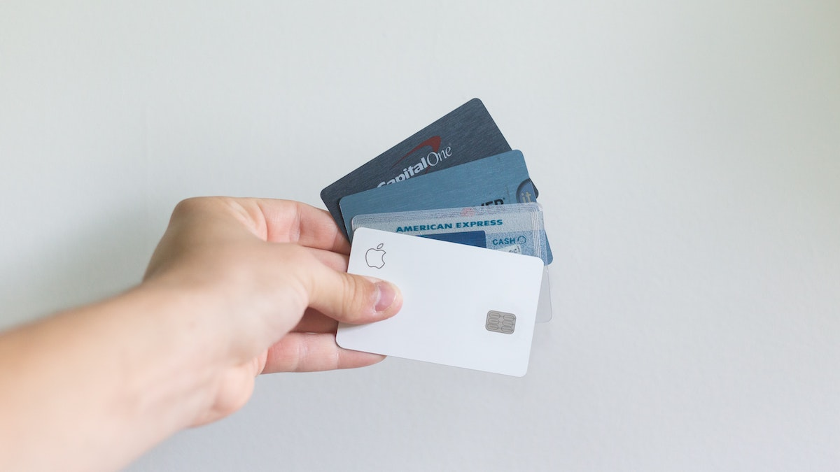A hand holding 4 different credit or debit cards.