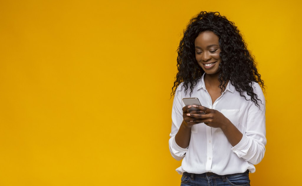 Confident Black woman with long naturally curly hair wearing a white blouse and smiling while looking at phone and texting.