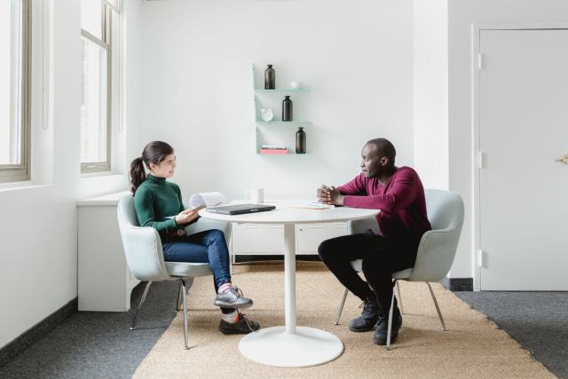 A man and a woman talking during a 1:1 meeting