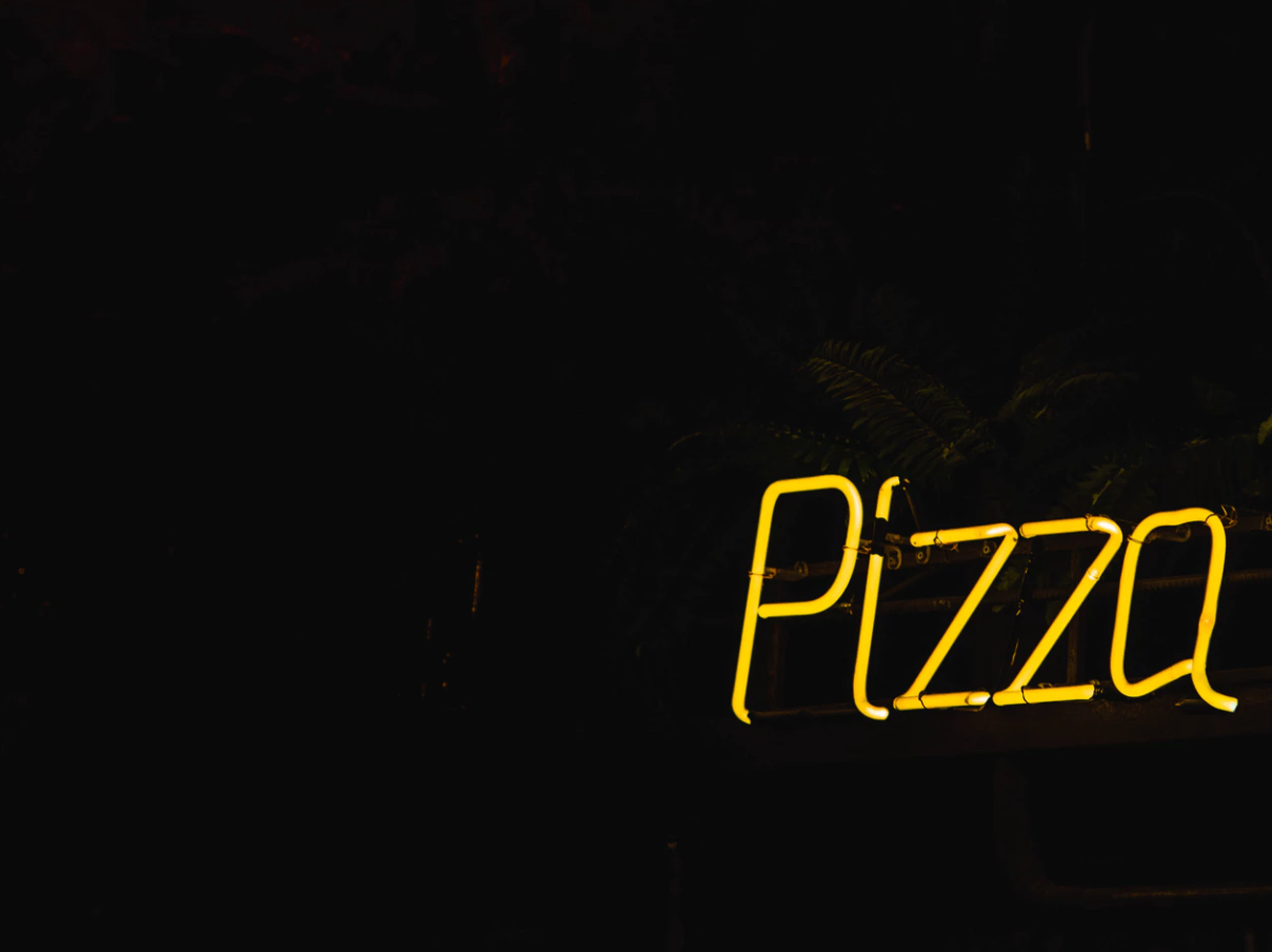 "Yellow neon sign that reads ""Pizza"""