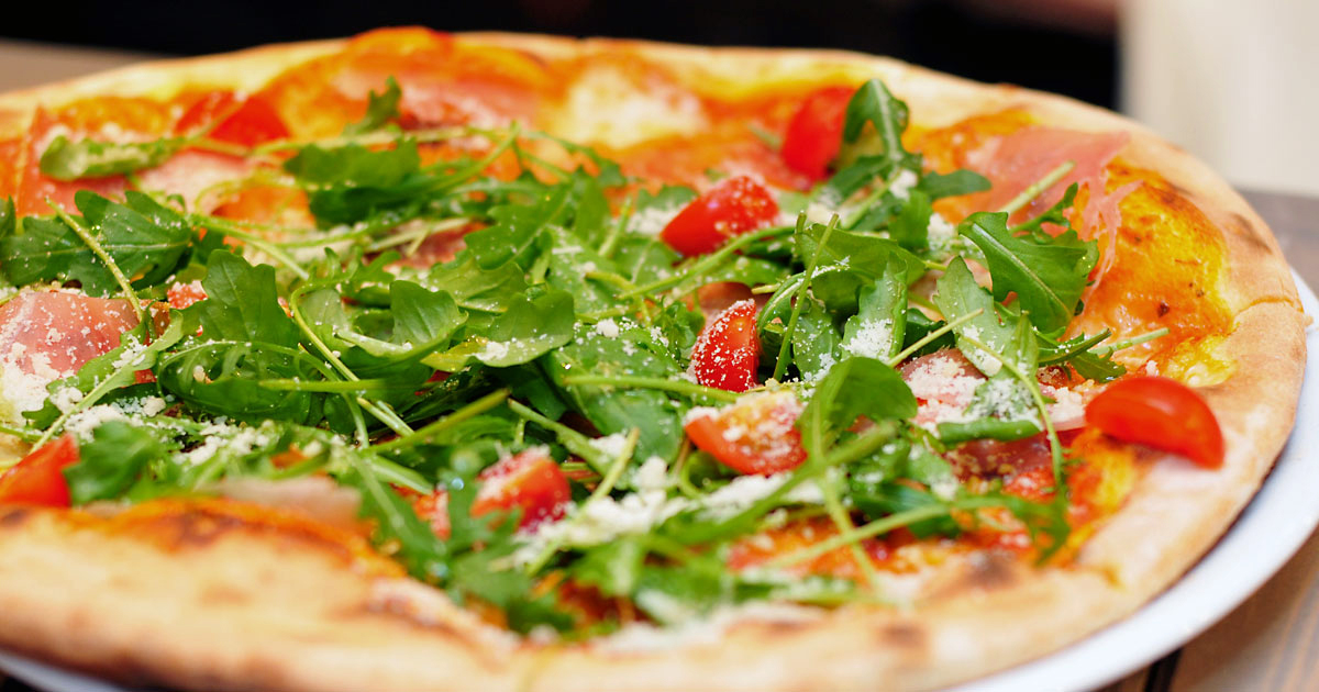 Pizza with arugula and fresh tomatoes