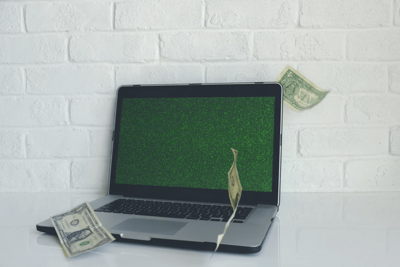 Laptop with floating dollar bills