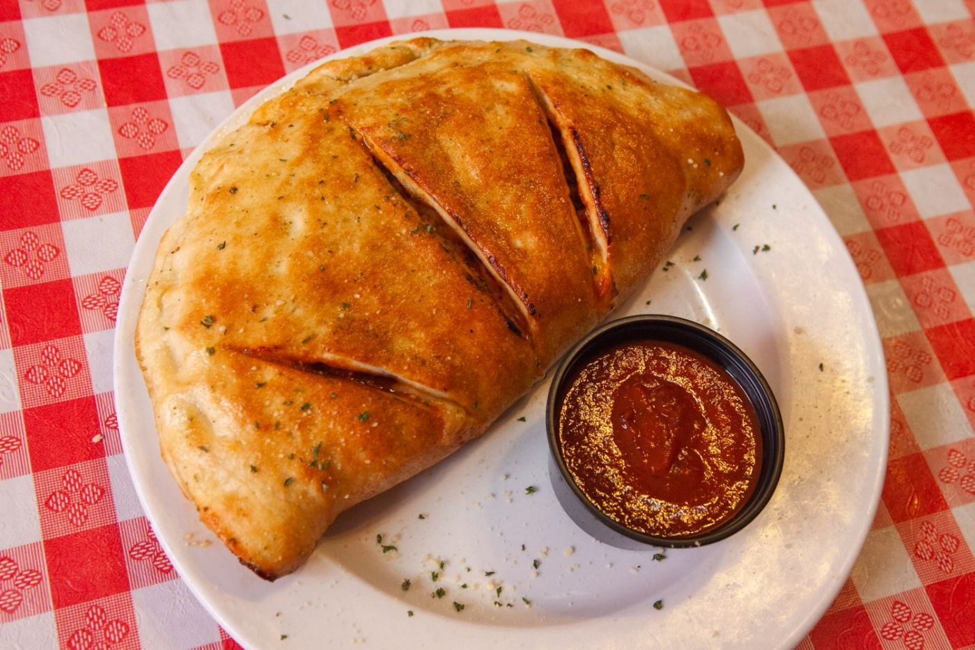 Calzone on a plate with a cup of marinara