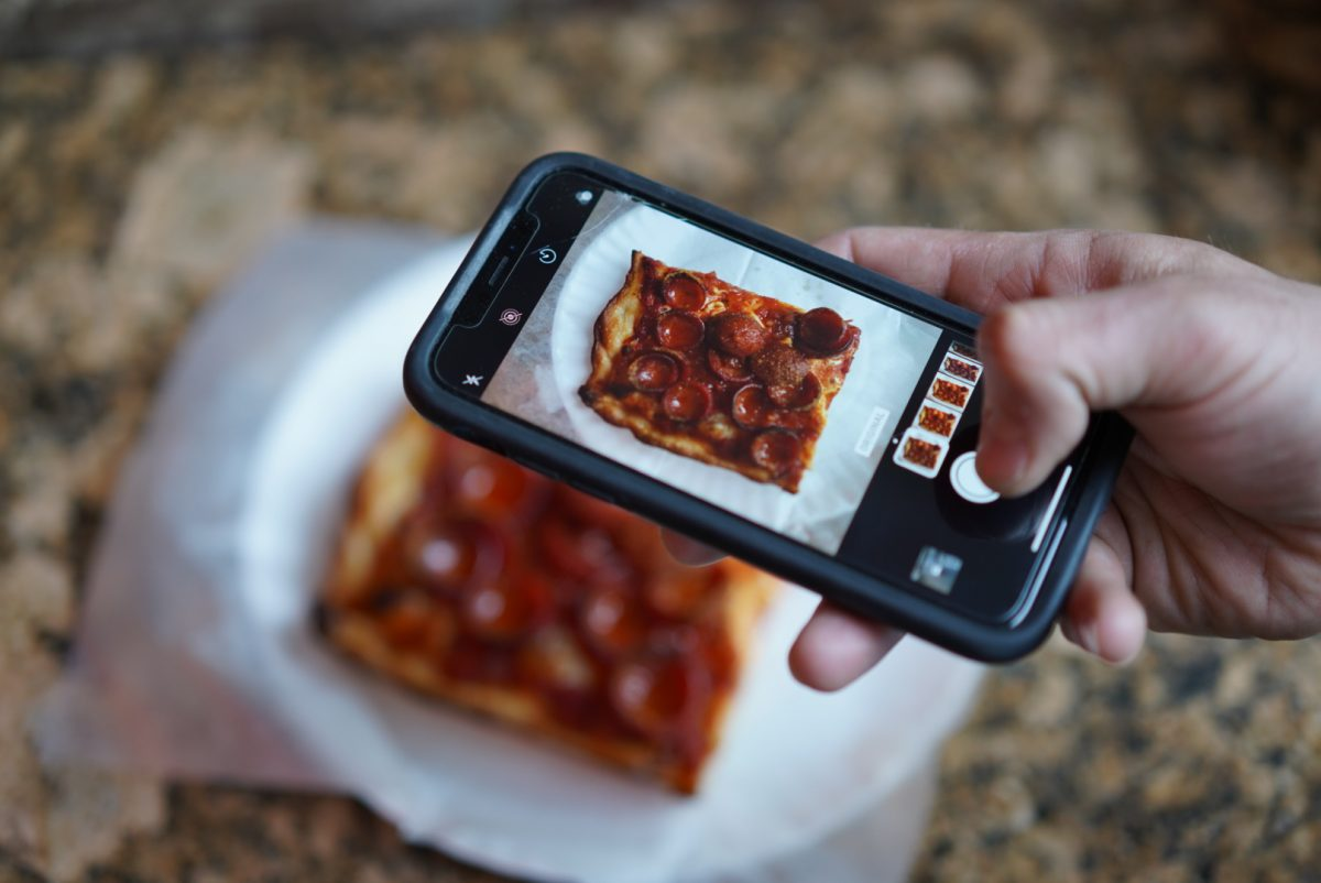 Taking a photo of pizza on Instagram App Credit: Ryan John Lee